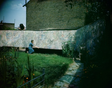 Colour photo from 1947 showing a woman in garden hanging a hug painted fabric on fence with her son behind helping to suspend.