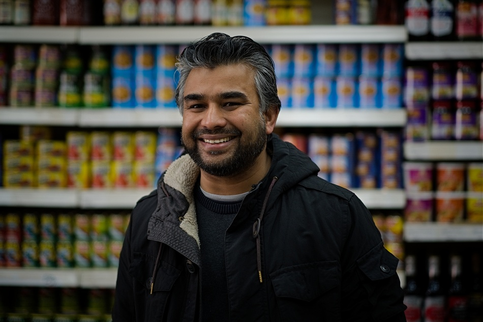 Mohammed, owner of Miah's Oriental Foods (East London) in his shop, © Keith Martin for the Migration Museum