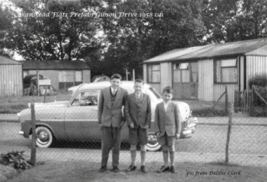 Black and white photo of family standing in front of prefabricated houses in Wansted Flats, East London